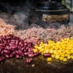 Mais, Reis, Bohnen und Hackfleisch braten auf der Feuerplatte von Monolith